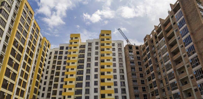 De bouw en werkende kraan van de hoge het toenemen woonflatbaksteen met meerdere verdiepingen op blok in aanbouw op blauwe hemela royalty-vrije stock afbeelding