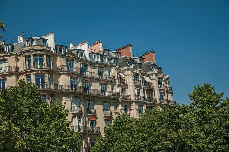 De bouw in het midden van bomen en zonnige blauwe hemel met Parijse architectuur van Parijs royalty-vrije stock afbeeldingen