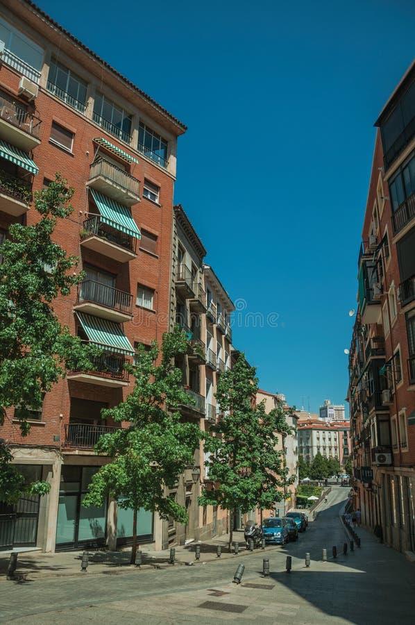 De bouw met bakstenenvoorgevel en bomen op een stille straat in Madrid royalty-vrije stock afbeeldingen