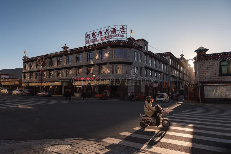 De bouw van de Daochengarchitectuur met verkeer op weg bij zonsondergang stock afbeelding