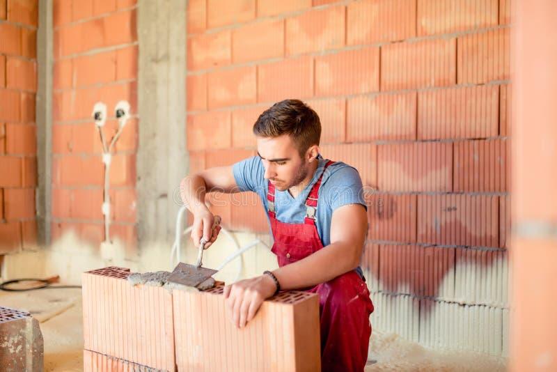 De bouw van de metselaarbouwvakker bakstenen muren, contractant die huis vernieuwen Bouwnijverheidsdetails royalty-vrije stock foto