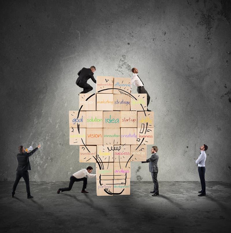 De bouw van een nieuw creatief idee De bedrijfspersoon bouwde samen een grote bakstenen muur met getrokken lightbulb stock fotografie