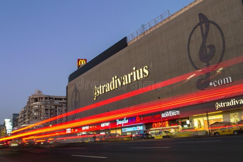 De bouw van het Unireawinkelcentrum in het centrum van de hoofdstad van Roemenië, bij nacht, met gele die cabines vooraan worden  stock afbeeldingen