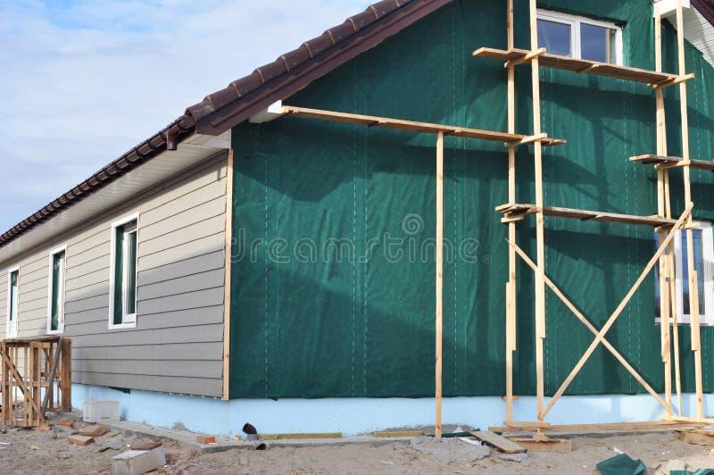 De bouw van huis met muurisolatie, waterpfoof membraan, plastic het opruimen, het guttering en stichtingsisolatie met storaxschui royalty-vrije stock afbeeldingen
