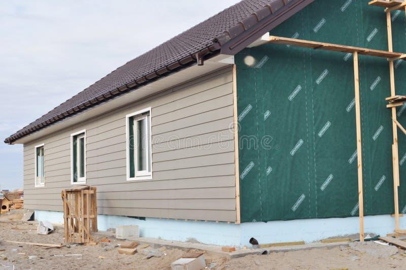 De bouw van huis met muurisolatie, waterpfoof membraan, plastic het opruimen, het guttering en stichtingsisolatie met storaxschui stock afbeelding
