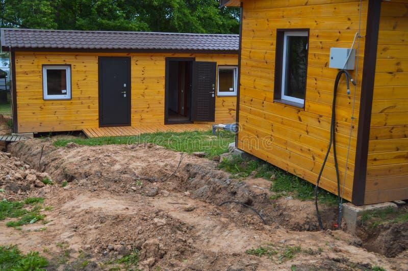 De bouw van klein geel houten kader prefabriceerde geprefabriceerd eco-huis van modulaire snelgroeiende huizen in de voorsteden stock foto