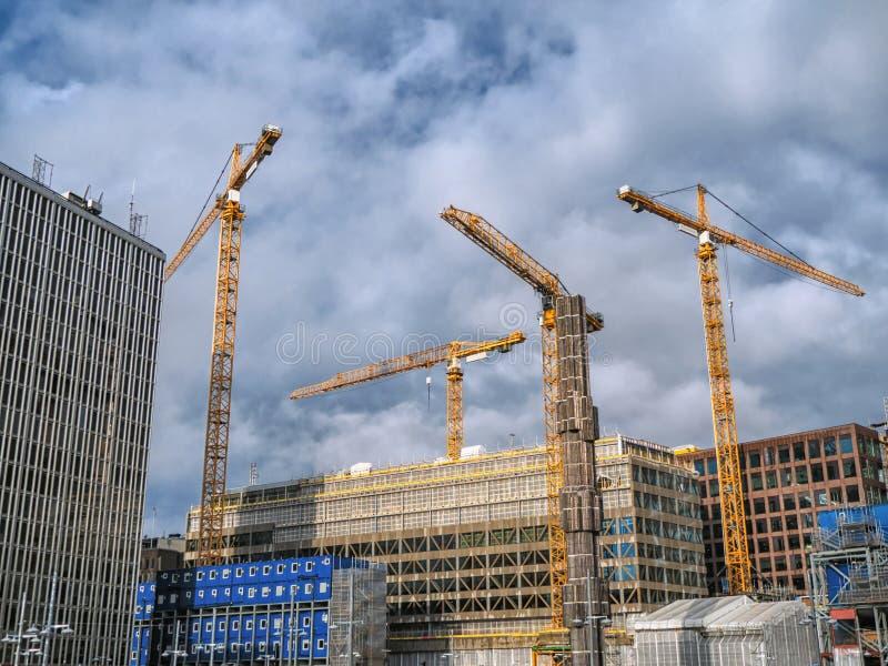 De bouw van kranen die nieuwe bouwconstructie bouwen op de bewolkte achtergrond royalty-vrije stock fotografie
