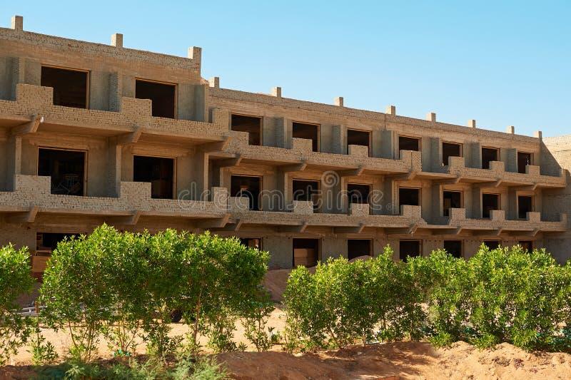 De bouw van nieuwe moderne woningbouw, arbeiders giet beton in houten kader royalty-vrije stock afbeelding