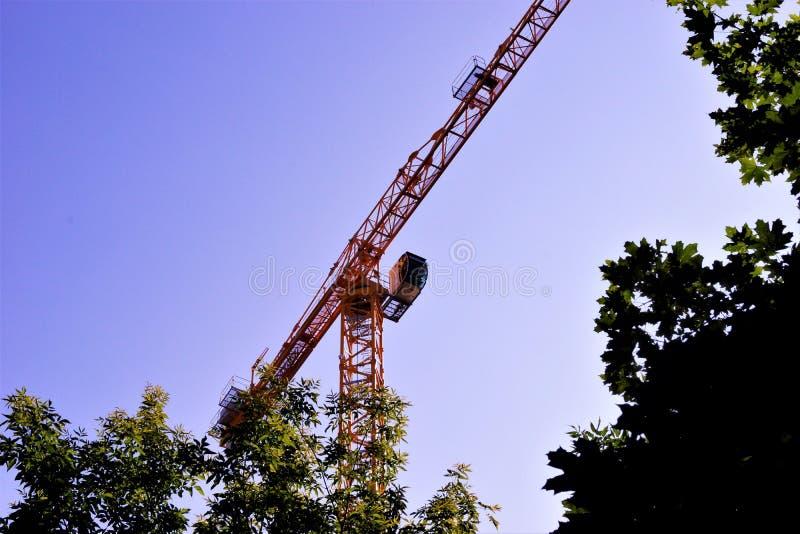 De bouw van de torenkraan roterend met een pijl op de achtergrond van de hemel en de bomen Het opheffen van machine ruimteverkeer stock fotografie
