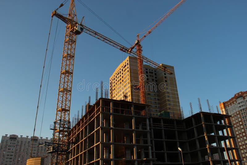 De bouw van a van een woningbouw met meerdere verdiepingen met twee torenkranen Bouw van een monolithisch kadergebouw stock fotografie