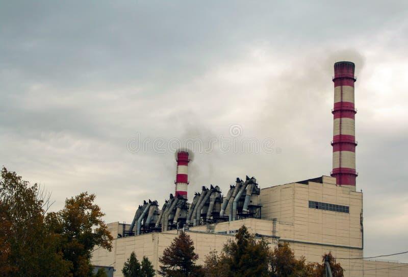 De bouw van de WKK is een warmtekrachtcentrale met buizen tegen een sombere lucht royalty-vrije stock afbeelding