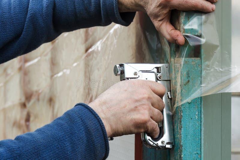 De bouwer bevestigt polyethyleenfilm met voornaamste kanon stock afbeelding