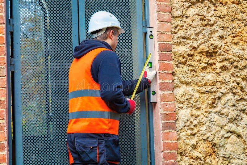 De bouwer controleert het deurniveau stock fotografie