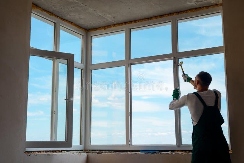 De bouwer installeert een venster stock afbeelding