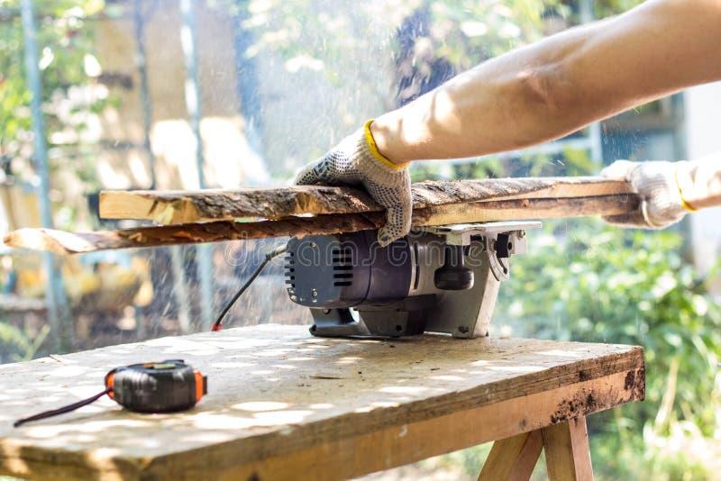 De bouwer snijdt de raad met een cirkelzaag stock foto