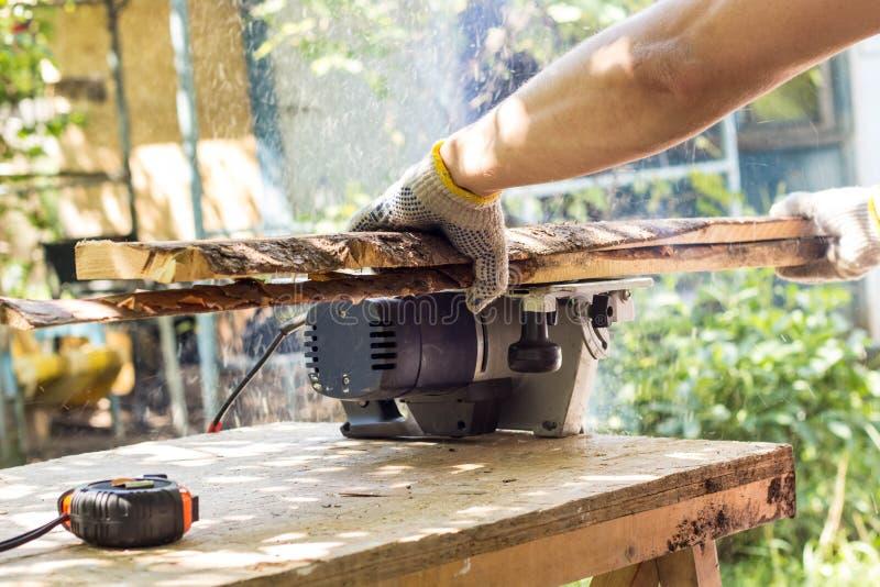 De bouwer snijdt de raad met een cirkelzaag stock foto's
