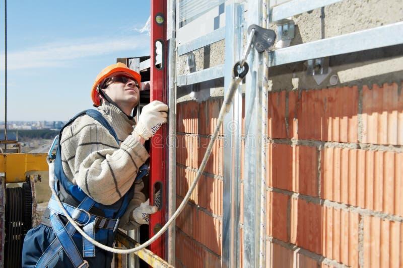 De bouwer van de arbeider aan de werk van de voorzijdebouw stock foto