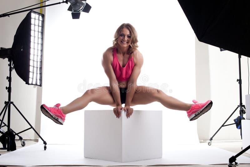 De bouwer van het de vrouwenlichaam van de schoonheid zit op kubus in studio royalty-vrije stock foto