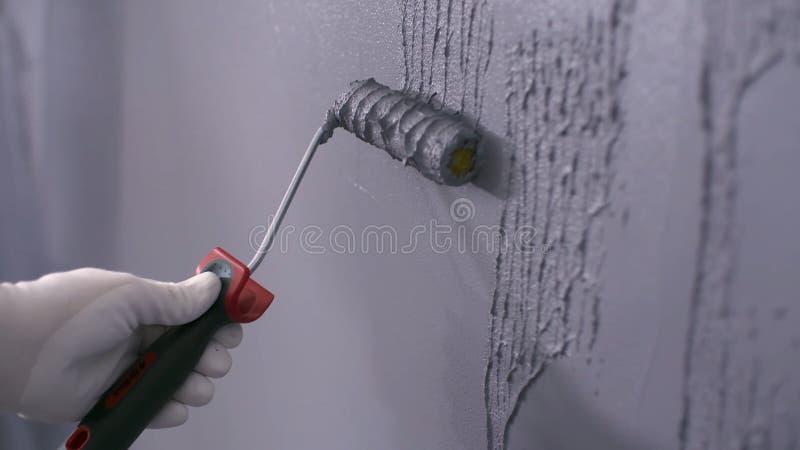 De bouwer zet decoratief pleister op de muur stock afbeelding