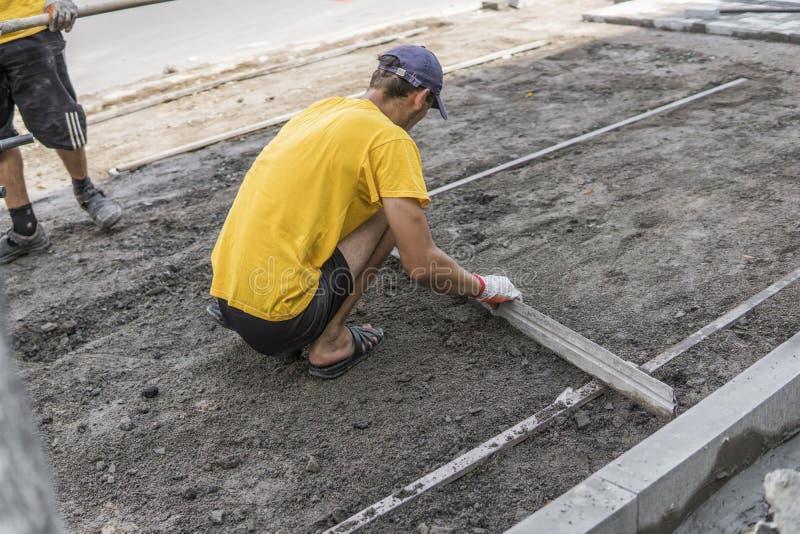De bouwer in zijn gloved sinaasappel en geel overhemd bereidt de oppervlakte voor alvorens de straatstenen met de heerser van te  stock afbeeldingen