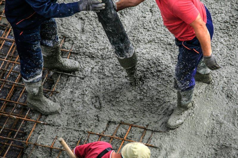 De bouwers werkt aan de bouwwerf: gietend beton voor FO stock afbeelding