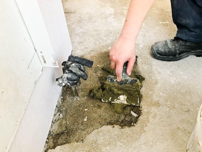 De bouwershanden met een metaalspatel pleisteren de muur, giet screed met pleister, tegellijm, cement voor de reparatie stock fotografie