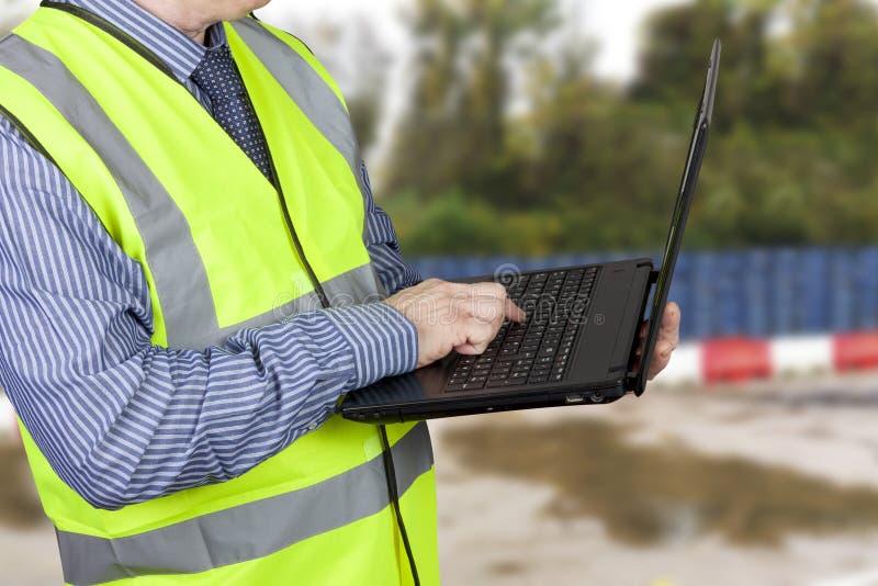 De bouwlandmeter in hallo vis bekleedt het ingaan van gegevens in zijn laptop stock afbeelding