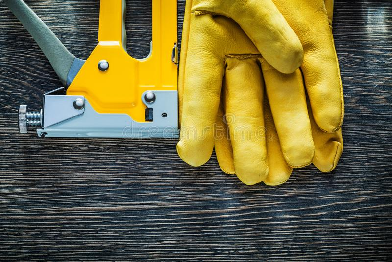 De bouwnietmachine van leer beschermende handschoenen op houten raad royalty-vrije stock foto's