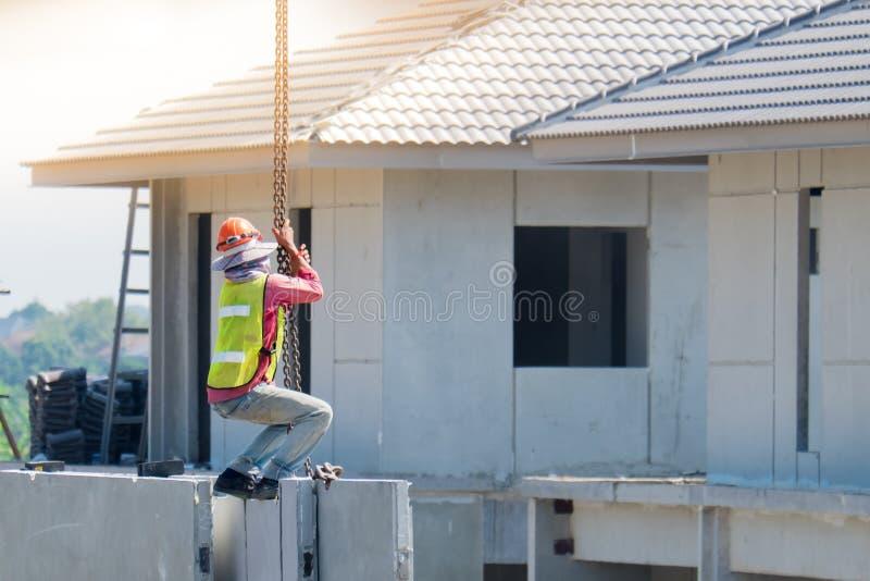 De bouwvakker installeert Kraanhaken bij de geprefabriceerde concrete muur, Geprefabriceerde huisbouw royalty-vrije stock foto's