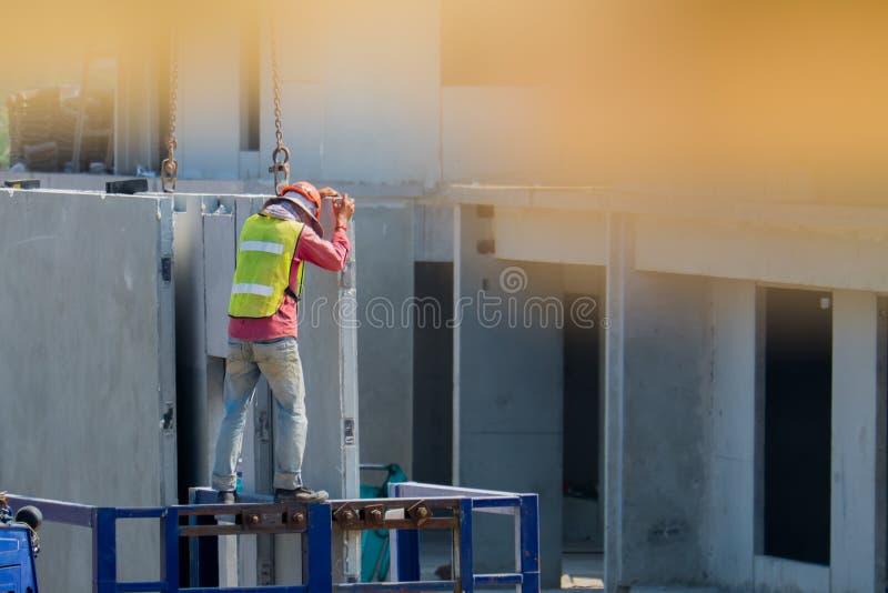 De bouwvakker installeert Kraanhaken bij de geprefabriceerde concrete muur, Geprefabriceerde huisbouw royalty-vrije stock afbeeldingen