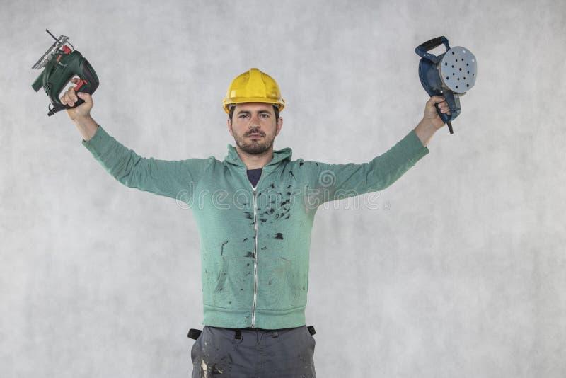 De bouwvakker toont de hulpmiddelen noodzakelijk voor zijn werk royalty-vrije stock afbeelding