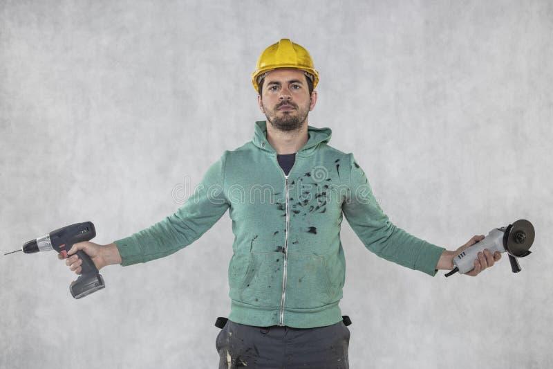 De bouwvakker toont de hulpmiddelen noodzakelijk voor zijn werk, vooraanzicht stock foto