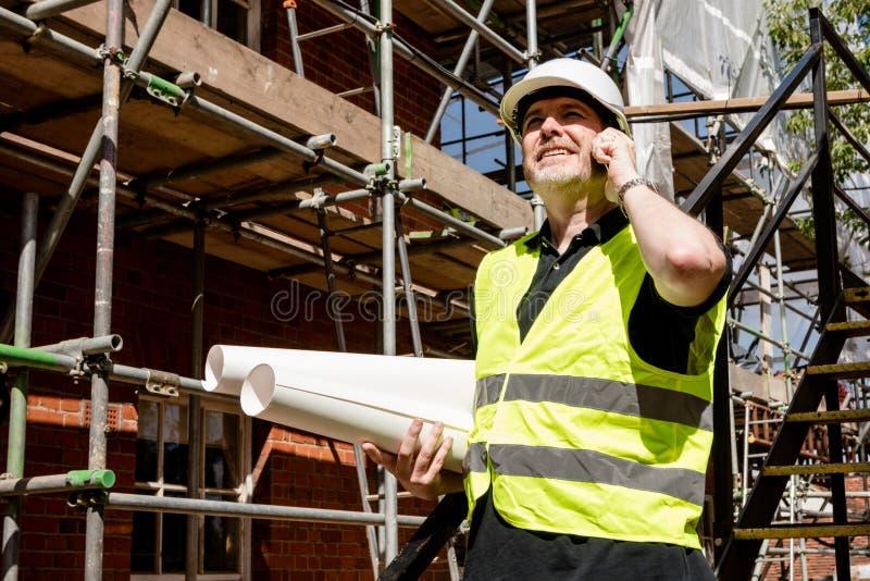 De bouwvakker, de voorman of de architect op bouwwerf die op zijn cel spreken telefoneren en gerolde bouwtekeningen houden royalty-vrije stock foto