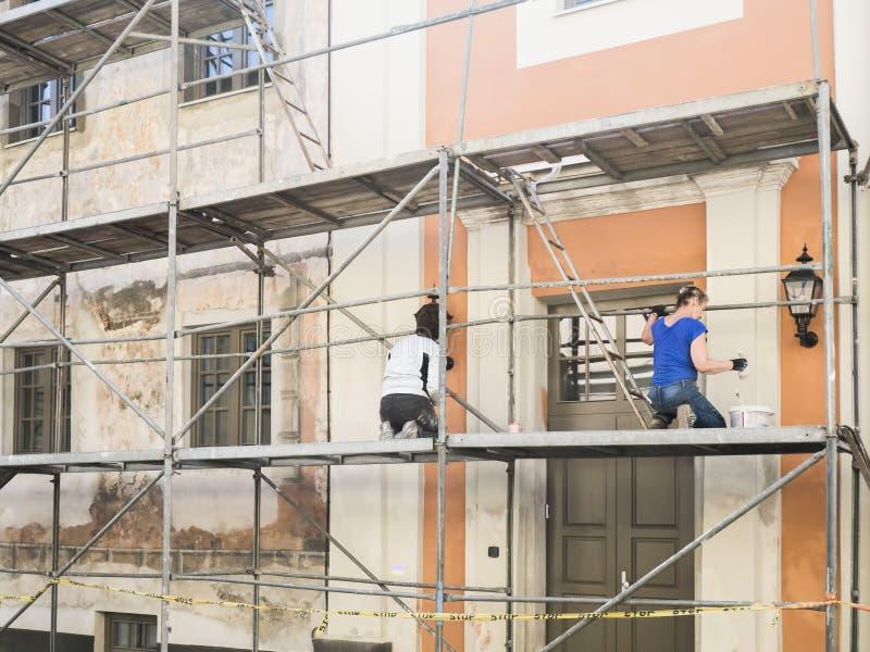 De bouwvakkers in steiger van de oude de bouwvoorgevel voor herstellen en vernieuwen royalty-vrije stock foto