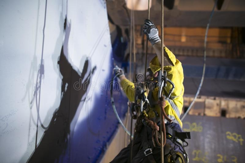 De bouwvakkerschilder die van de kabeltoegang bij hoogte werken royalty-vrije stock afbeeldingen