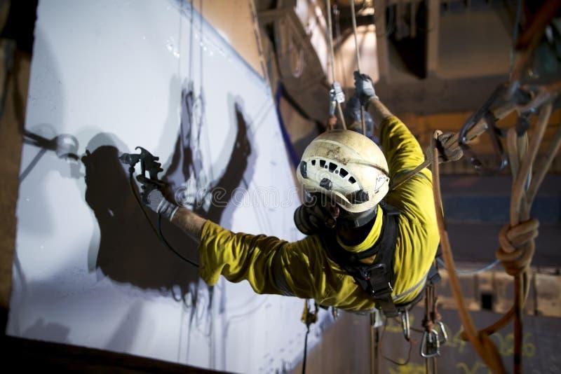 De bouwvakkerschilder die van de kabeltoegang bij hoogte werken royalty-vrije stock afbeelding
