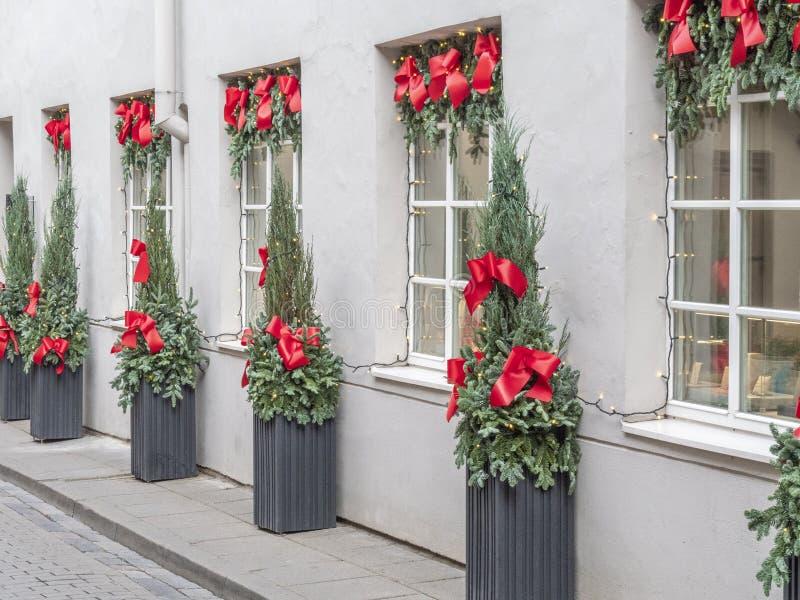 De de bouwvoorzijde aan Kerstmis met de spar van Kerstmisbomen wordt verfraaid vertakt zich, decoratie en slingerlichten dat stock afbeelding