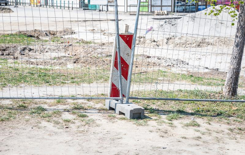 De bouwwerfbarri?re van het wegwerk vooruit met metaal beschermende omheining op de stedelijke straatherstelling in de stad stock fotografie