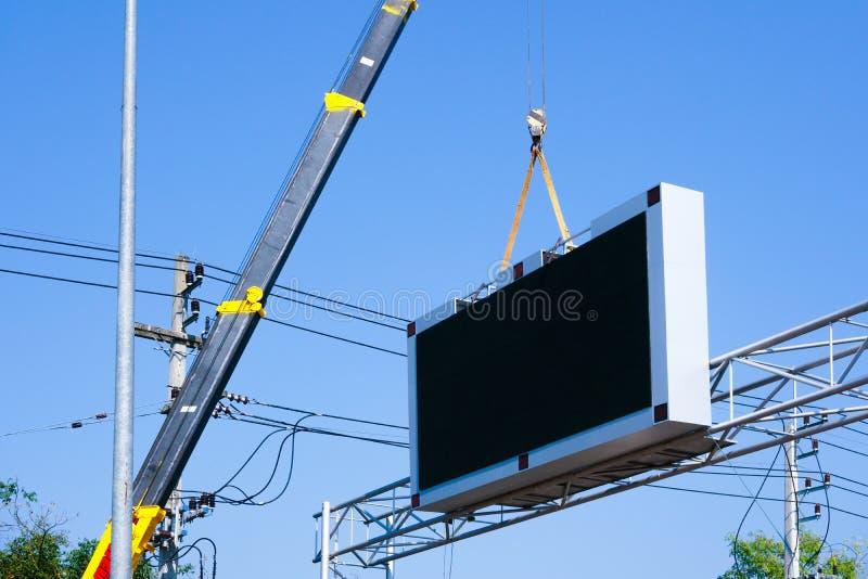 De bouwwerfkraan heft een geleid uithangbord Leeg aanplakbord op blauwe hemelachtergrond voor op nieuwe reclame stock foto's
