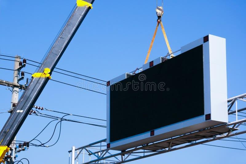 De bouwwerfkraan heft een geleid uithangbord Leeg aanplakbord op blauwe hemelachtergrond voor op nieuwe reclame royalty-vrije stock foto's