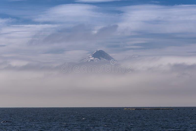 De bovenkant van de Osorno-vulkaan die in de wolken voorbij het Llanquihue-meer in Frutillar toeneemt royalty-vrije stock foto