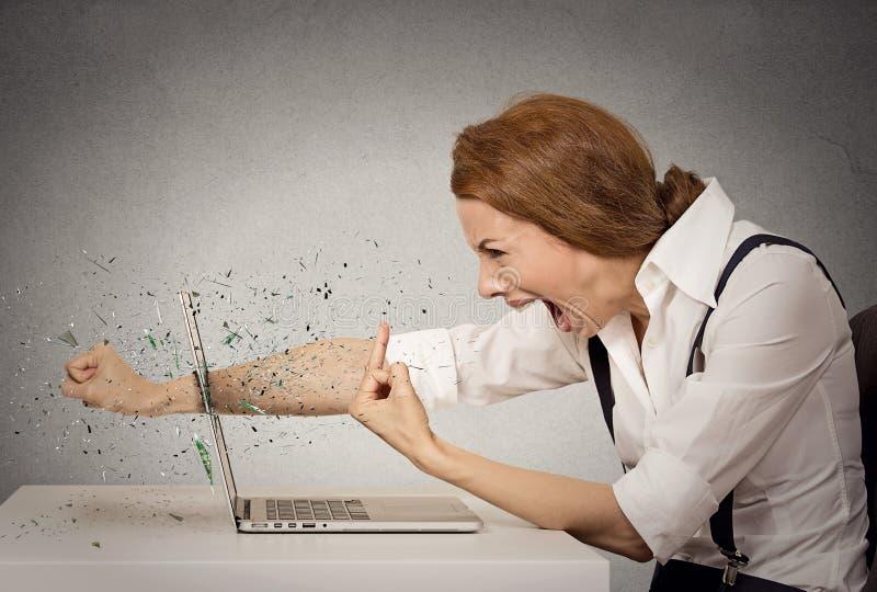 De boze bedrijfsvrouw werpt stempel in computer, het gillen royalty-vrije stock fotografie