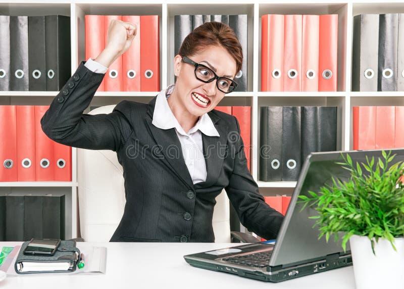 De boze bedrijfsvrouw wil computer breken stock foto's