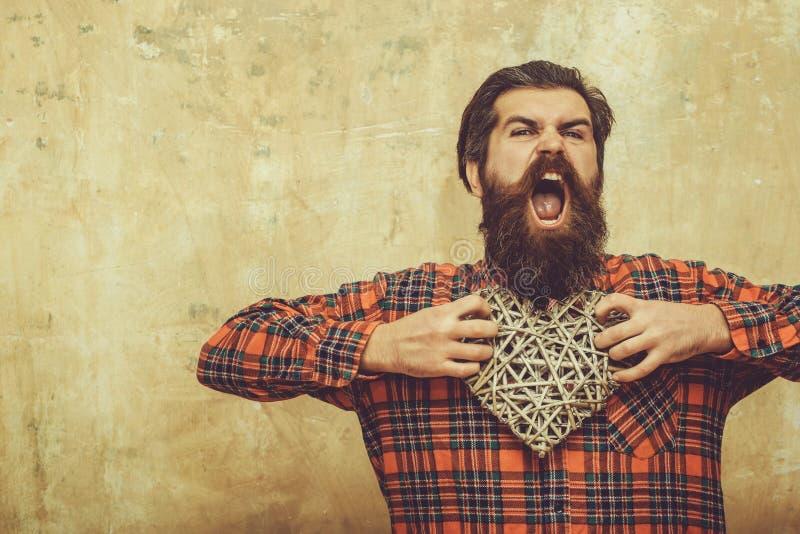De boze gebaarde mens met lange baard houdt rieten hart royalty-vrije stock fotografie