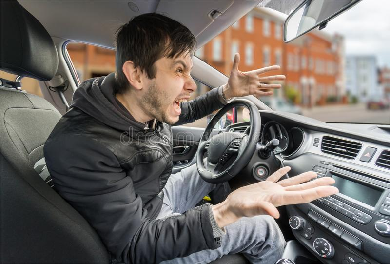De boze jonge bestuurder drijft een auto en het schreeuwen royalty-vrije stock afbeelding