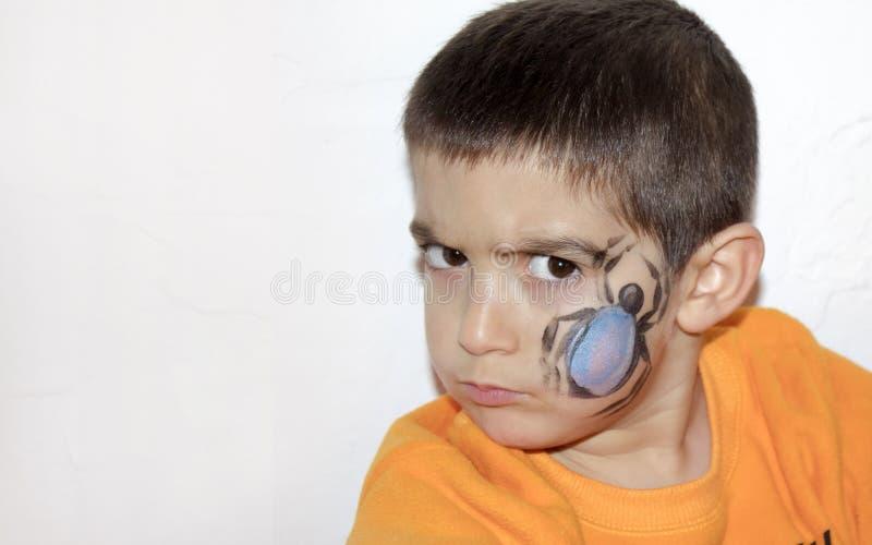 De boze jongen met gezicht schilderde met een spin stock fotografie