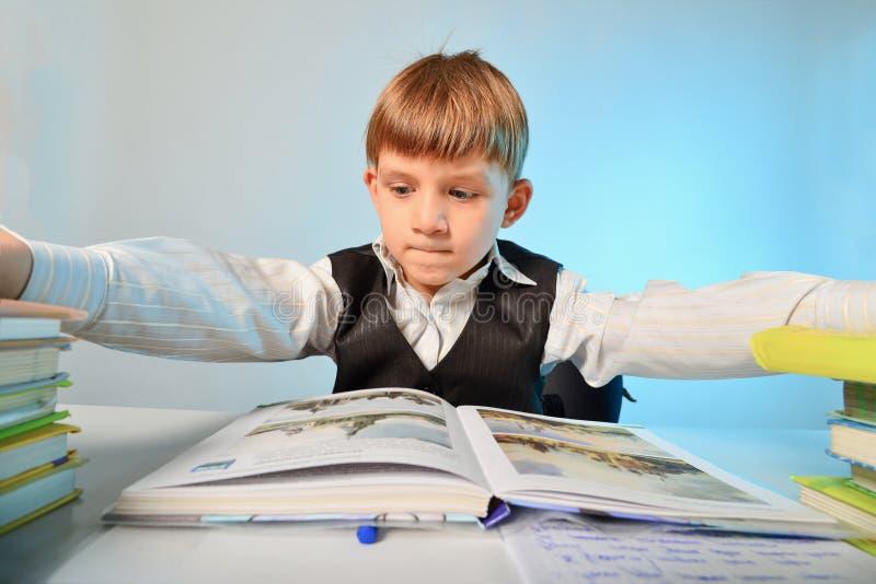 De boze jongen is vermoeid van het werk van de huisschool en duwt handboeken vanaf hem, brede hoekfoto stock foto