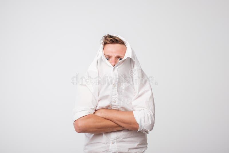 De boze Kaukasische mens trekt een wit overhemd over zijn hoofd eenzaamheid van gedeprimeerde persoon stock afbeelding