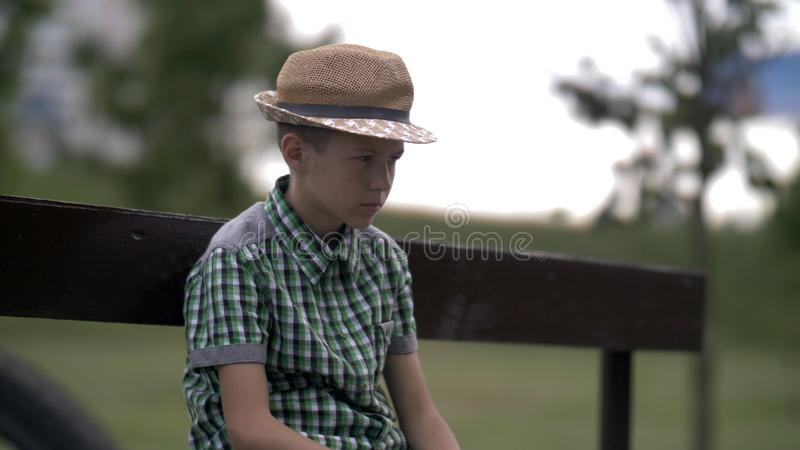 De boze, ongelukkige verdachte jongenszitting op een bank in het park, een jongen met een slechte familie, droevige jongen met ee royalty-vrije stock afbeelding
