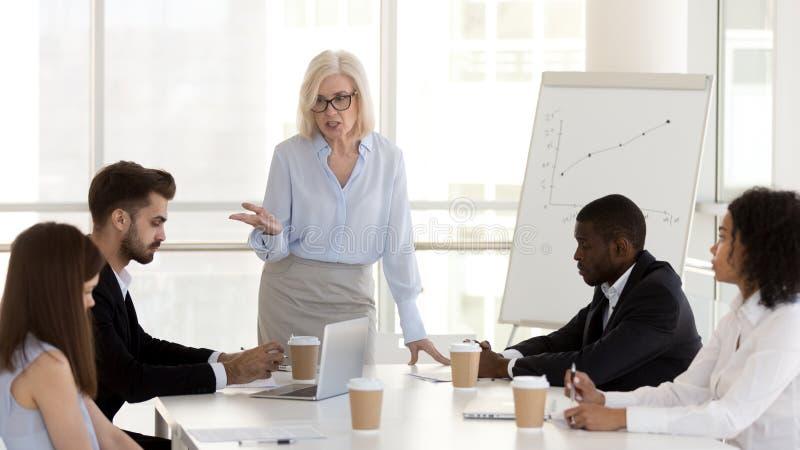 De boze rijpe onderneemster, werkgever berispt werknemers voor slechte het werkresultaten stock foto's